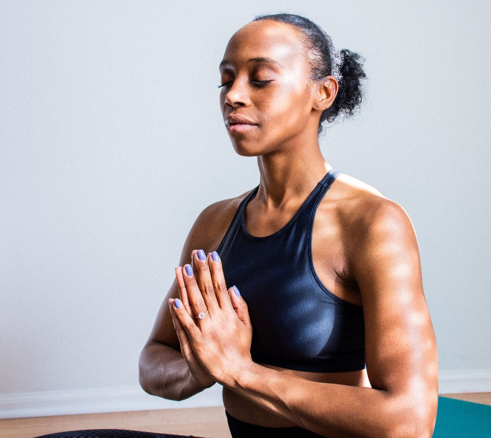 A woman sits in a basic stretching position with her palms touching.