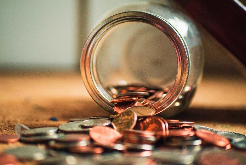 A glass jar of money rests on its side with a pile of different coins coming out of it.