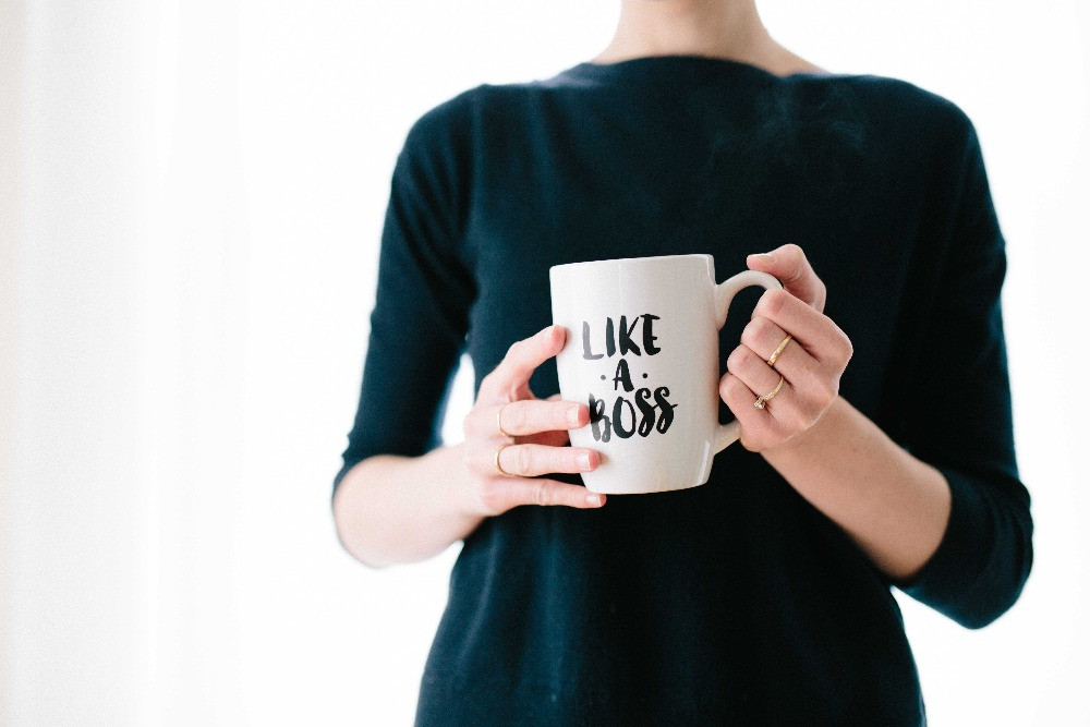 "A close-up shot of hands holding a white mug that says ""Like a Boss"" in black swirly script."