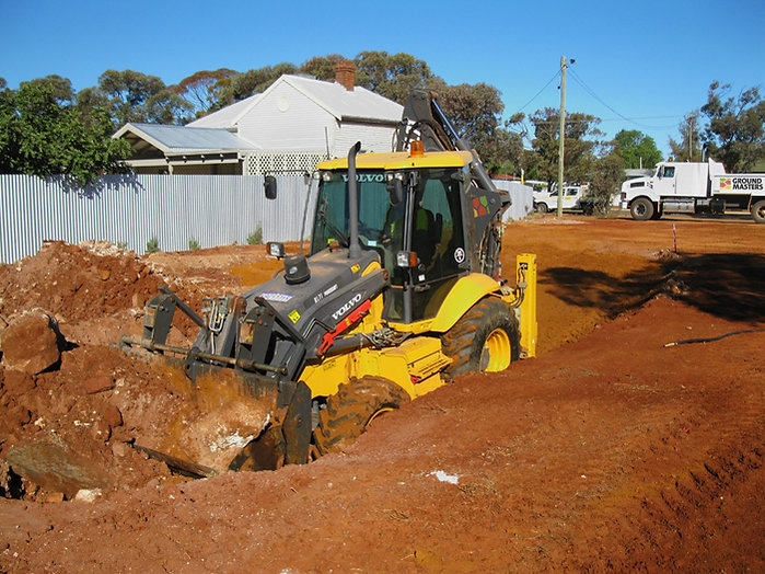 Ground Masters Volvo backhoe and International Tip Truck digging for house pad construction