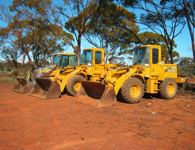 Ground Masters Volvo backhoe and Kawasaki Loaders resting between mining and exploration earthworks