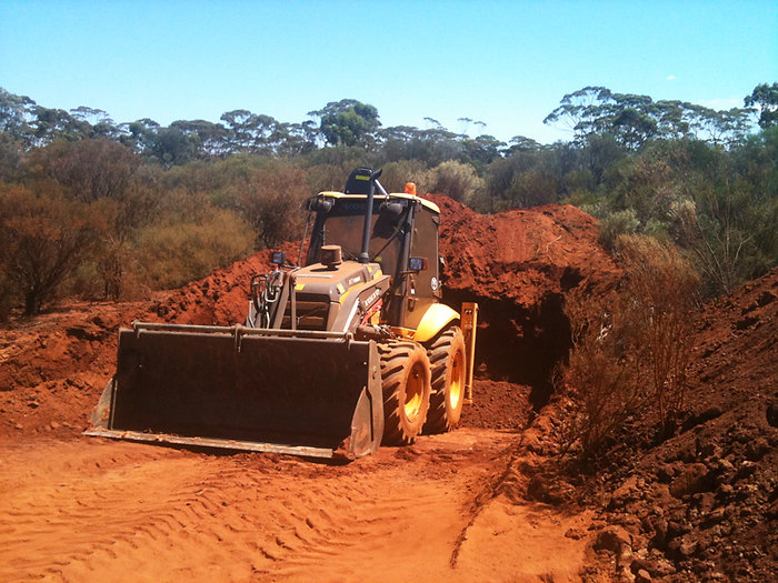 Ground Masters Volvo backhoe digging sump for drill site