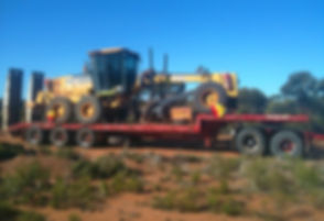 Ground Masters trailer transporting John Deere Grader