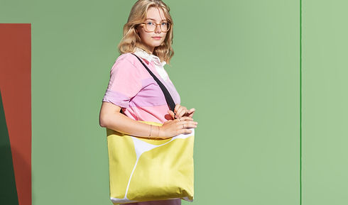 Girl wearing a yellow, modern tote bag on a green background.