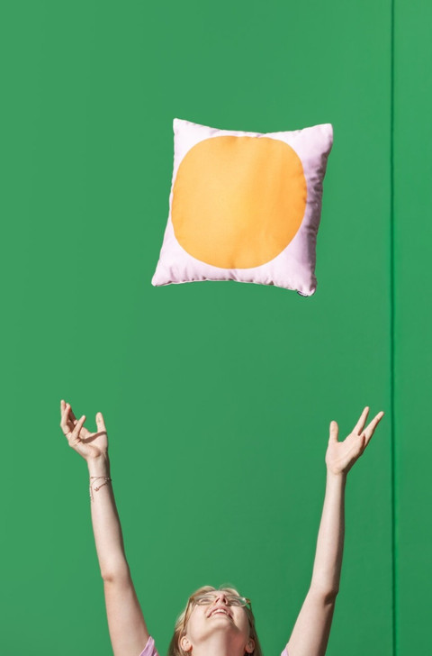 Girl throwing a pink pillow with orange circle up in the air against a green wall.