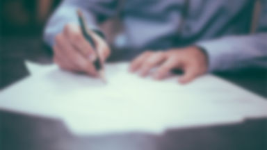 Someone signing a group of papers on a desk
