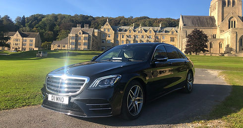 a black mercedes benz chauffeur car parked at a private school waiting for a client
