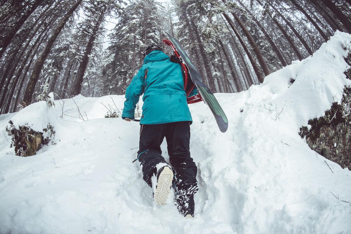 Snowboarder Walking Through Snow
