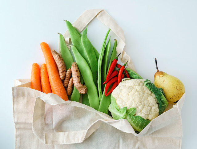 A bag of healthy fruit and vegetables, carrots, peas, beans, ginger, cauliflower, pears