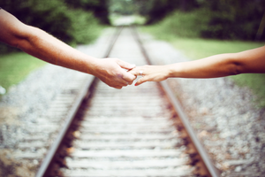 two people holding hands across a train track