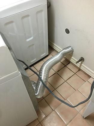 Behind washer and dryer.