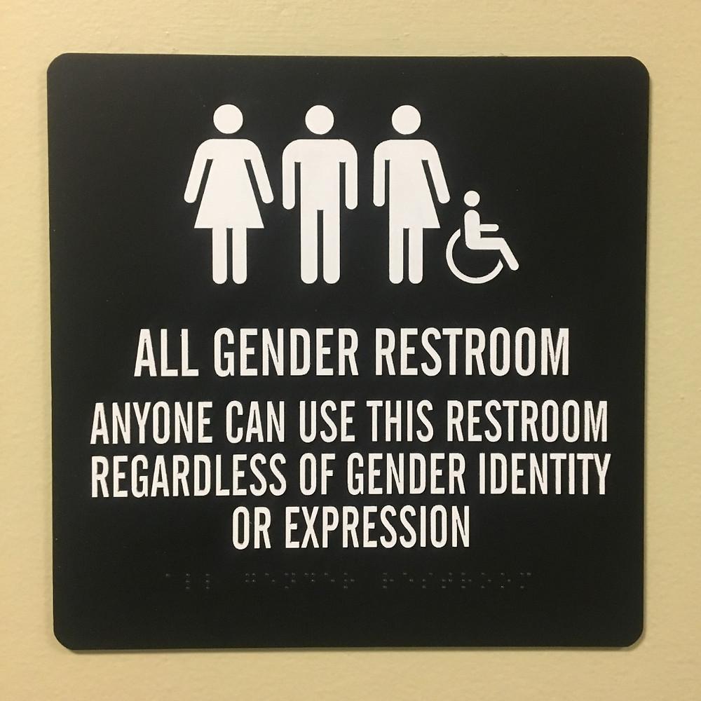 "Sign saying ""All gender restroom"" also written in braille"