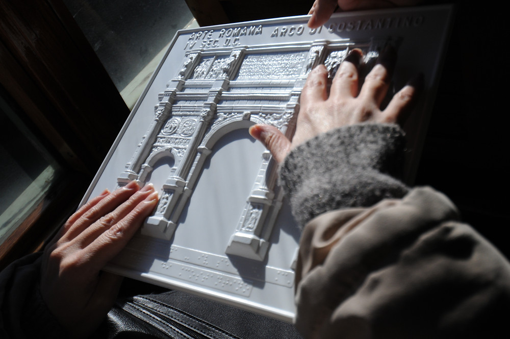 A 3D print of a monument with someone running their hands across it to feel the detail.