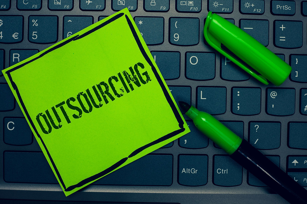 Picture of green Post-it note on laptop - Outsourcing Marketing Services article