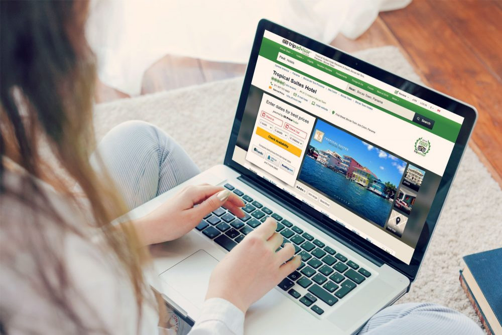 Picture of woman on laptop accessing TripAdvisor - Review Volume TripAdvisor Ranking Article