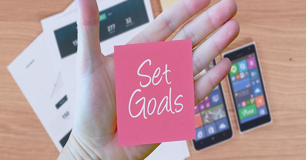 Man with Post-it note on hand that says set goals - Hotel Operations/Reviews Post