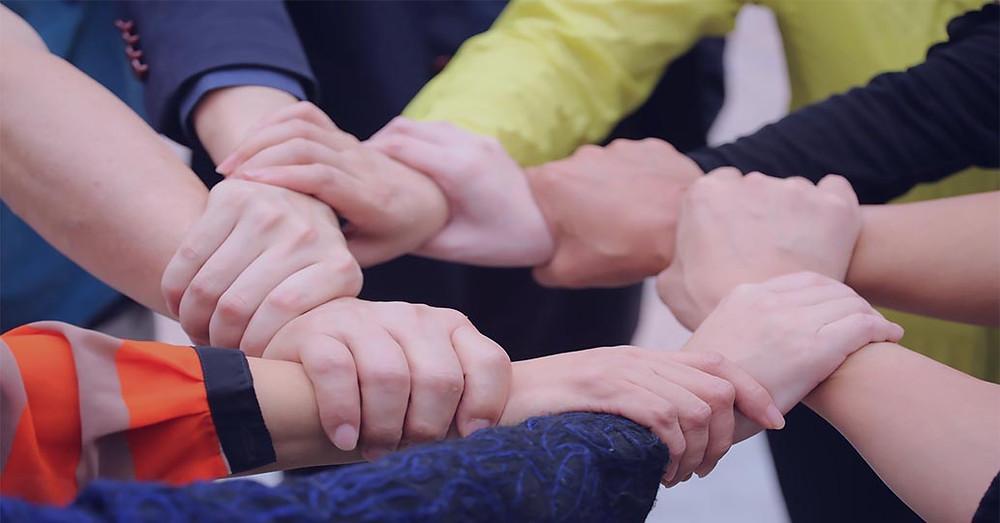 Picture of team interlocking hands - Team Goals article