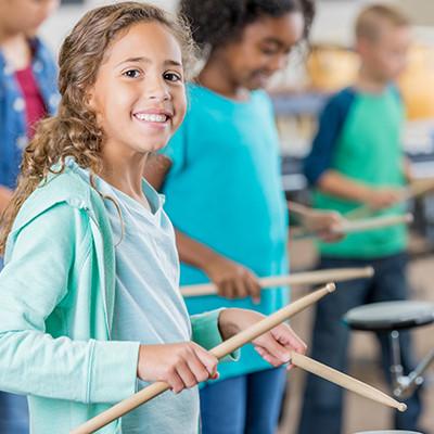 Elementary school student drumming in classroom.