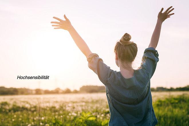 Junge Frau die ihre Arme nach oben streckt und auf dem Feld steht mit dem Schriftzug Hochsensibilitä