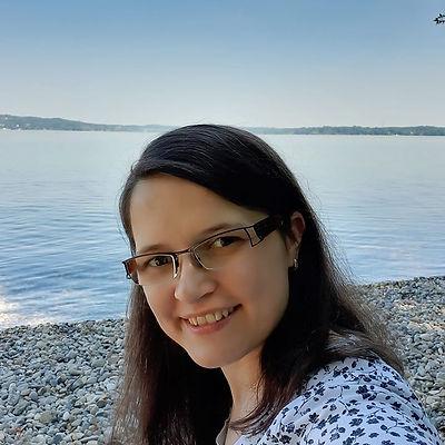 Junge Frau am See mit Brille und lächelnd
