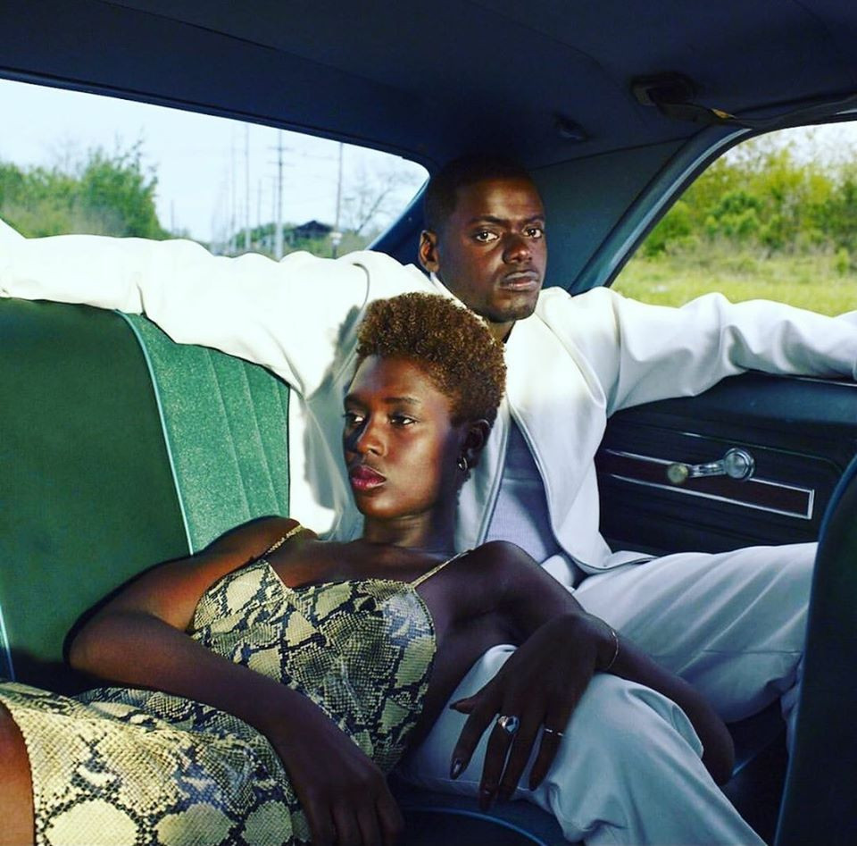 Woman and Man in the backseat of a car. Woman is wearing snake-skin print dress and man is in all white. The car has a green interior.
