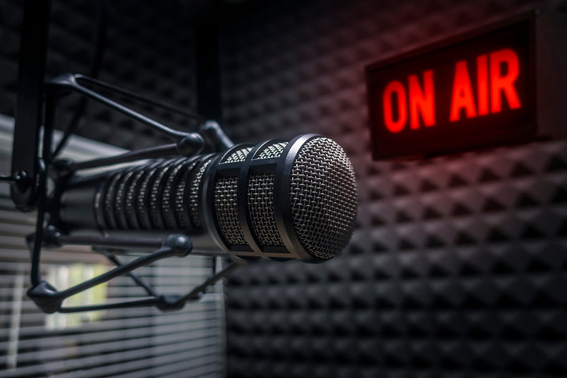 Professional microphone in radio station studio and on air sign.jpg