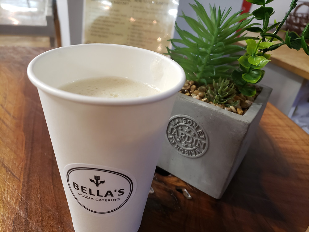A Sweet Potato Latte is inside an open coffee cup on a natural wood counter and an arrangement of succulents in the background.