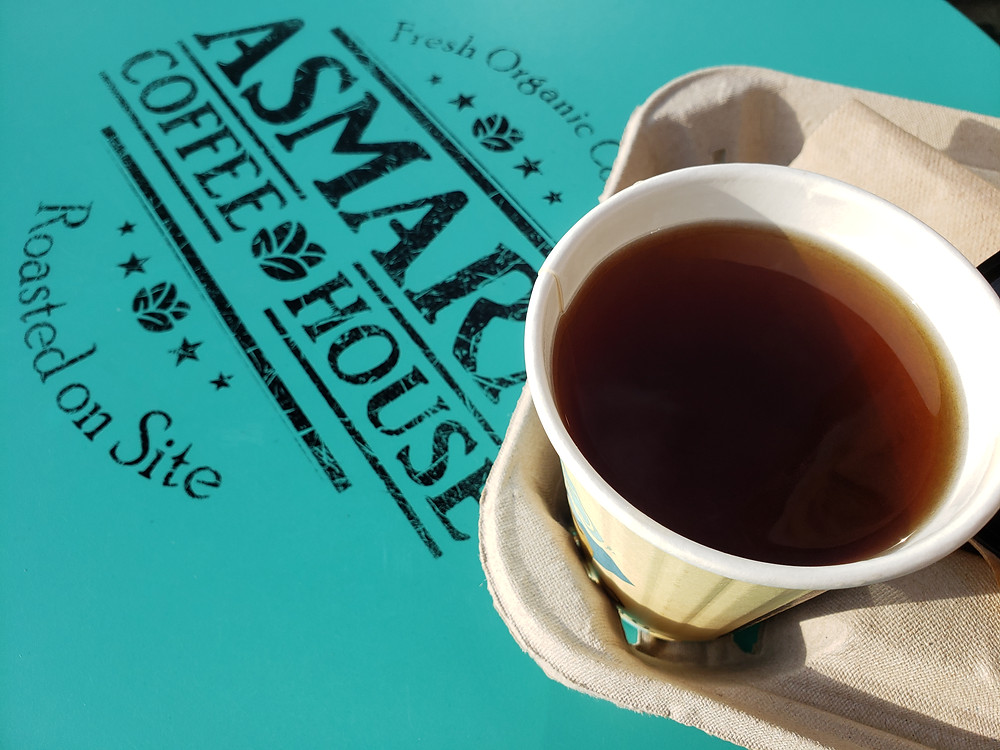 An open, steaming cup of warm apple cider is on a bright blue table with the Asmara Coffee House logo