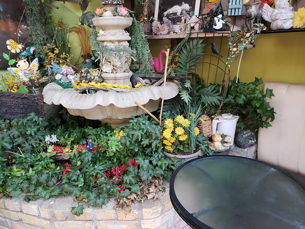 An indoor garden and fountain with the indoor seating at Maymo's Fry