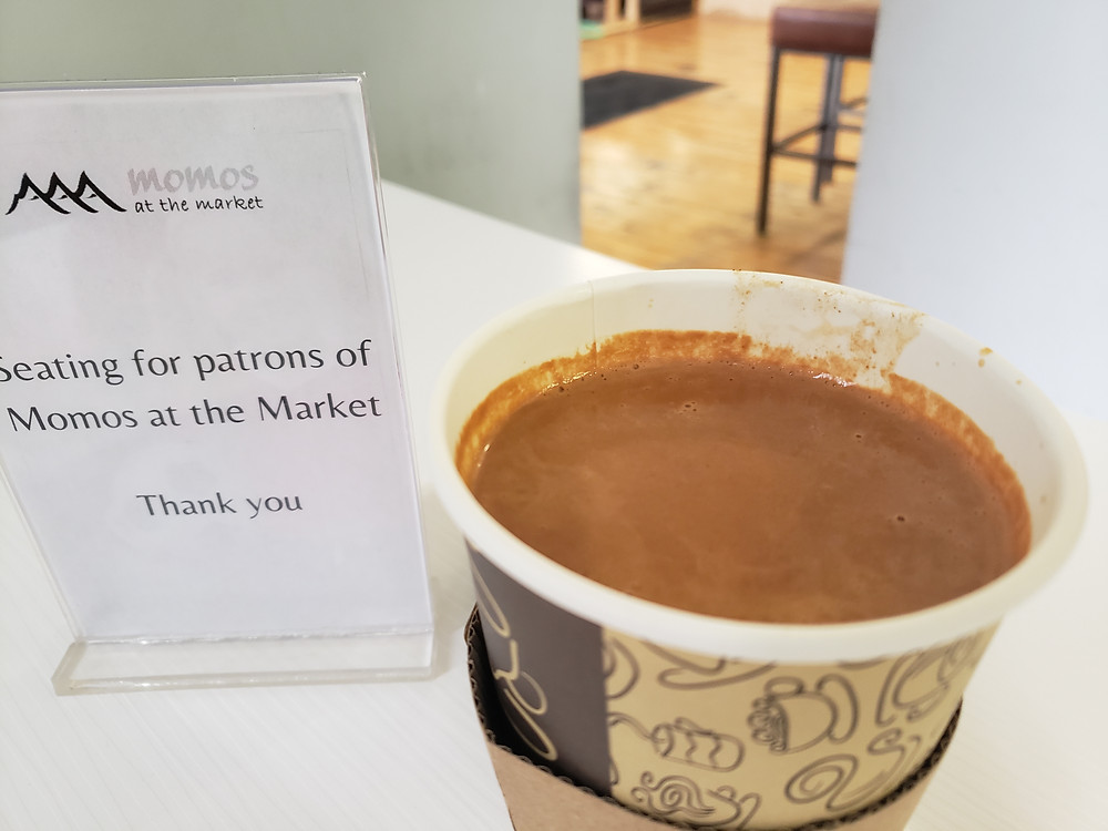 An open coffee cup filled with a dark, spicy tea is sitting on a white table