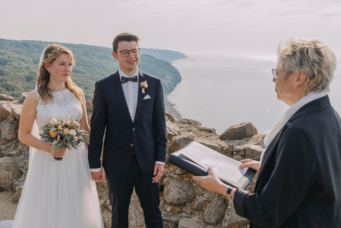 Newlyweds signing their paperwork during their full seaview wedding island ceremony on Bornholm Island while getting married in Denmark.