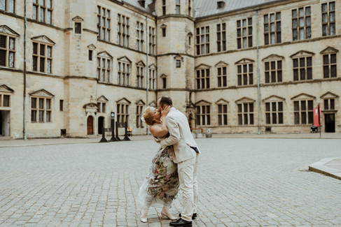 Husband and wife kissing during their Hamlet Castle wedding adventure, as they enjoy their Nordic wedding in Denmark.