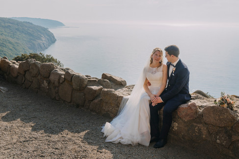 Newlyweds sitting at the edge of Hammershus Ruins while getting married overseas on Bornholm Island in Denmark, one of our best wedding packages abroad for two.