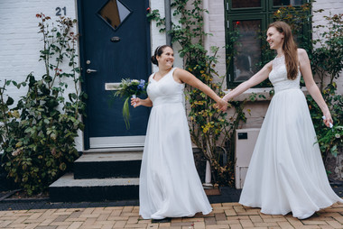 A lesbian couple holding hands and walking through Maribo as they enjoy getting married in Denmark