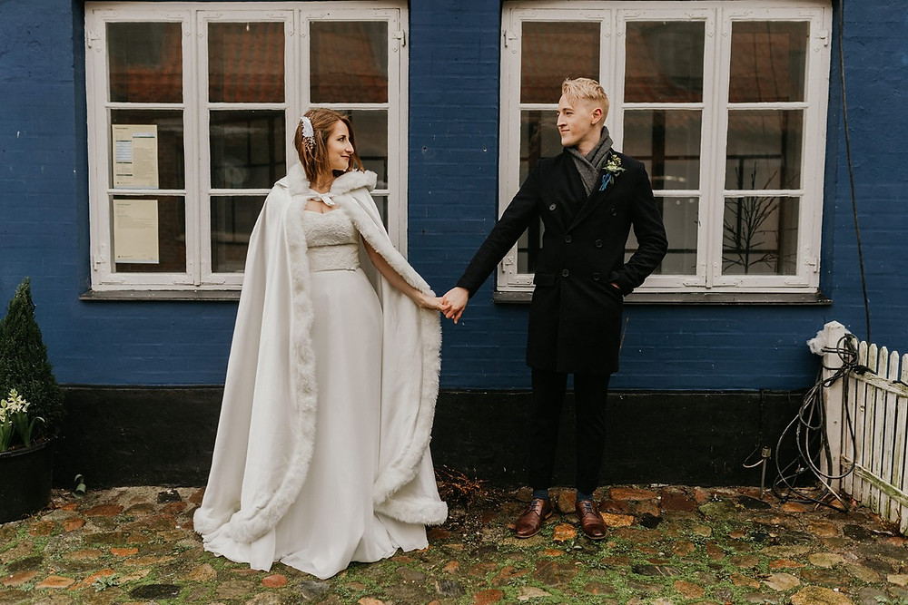 A bride and groom hold in hands and look at each other while they getting married in Denmark