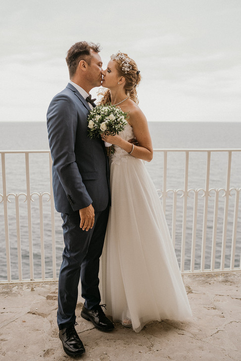 Newlyweds kissing during their small wedding abroad at Stevens Klint.