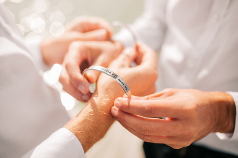 A groom placing an eternity bracelet on his partner's wrist as they enjoy their gay marriage in Denmark.