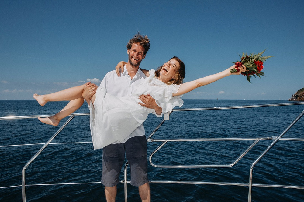 happy husband raises his wife in his arms, since they just had Scandinavian wedding on Bornholm