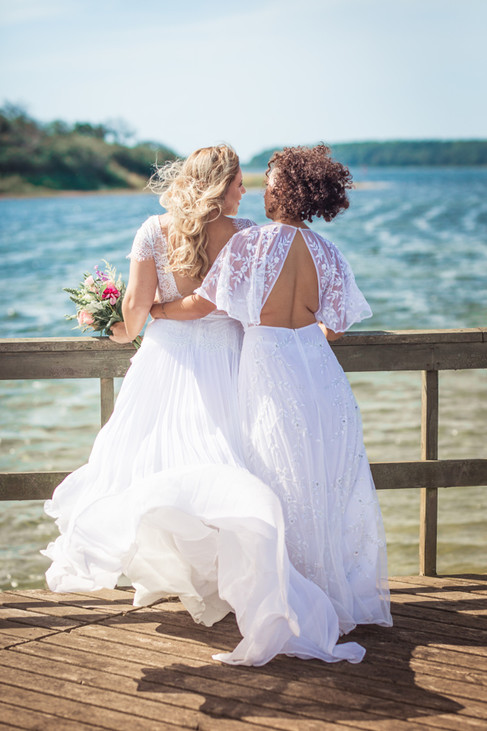 A same-sex couple during their bohemian wedding adventure in Denmark by the beach.