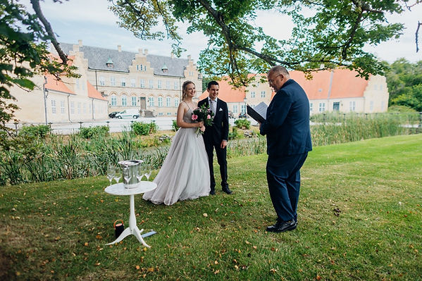 A couple getting married at a park in front of a castle at Lolland Island as their chosen destination wedding venue.