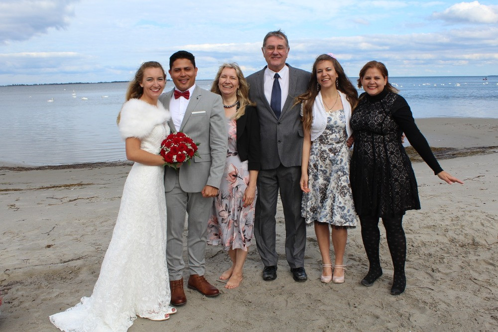 Guests participating in small beach wedding.