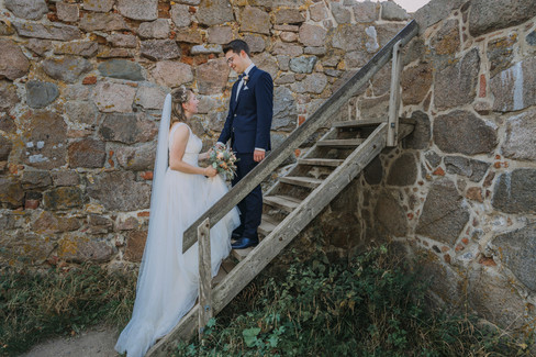 An intimate moment between husband and wife as they climb up the wooden stairs at the Hammershus Ruins during their Scandinavian wedding adventure.
