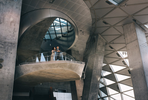 A couple standing on a round futuristic balcony, making their urban vows renewal idea a reality, a stunning building perfect for destination weddings for those seeking an urban Denmark wedding venue.