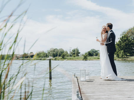 The bride and the groom eloping abroad, pictured by the Maribo Lake preparing for their outdoor wedding ceremony on the Danish bridal islands.