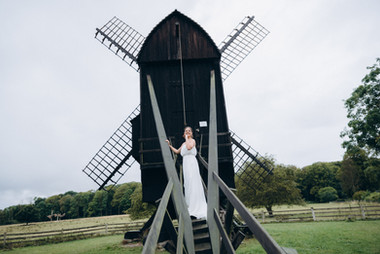 A bride on a windmill during her elopement in Denmark, one of the best places to get married abroad.