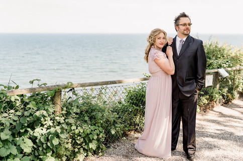 Newlyweds in front of the Baltic Sea, a panoramic view from Stevens Klint, a romantic and natural location for your intimate wedding abroad in Denmark.