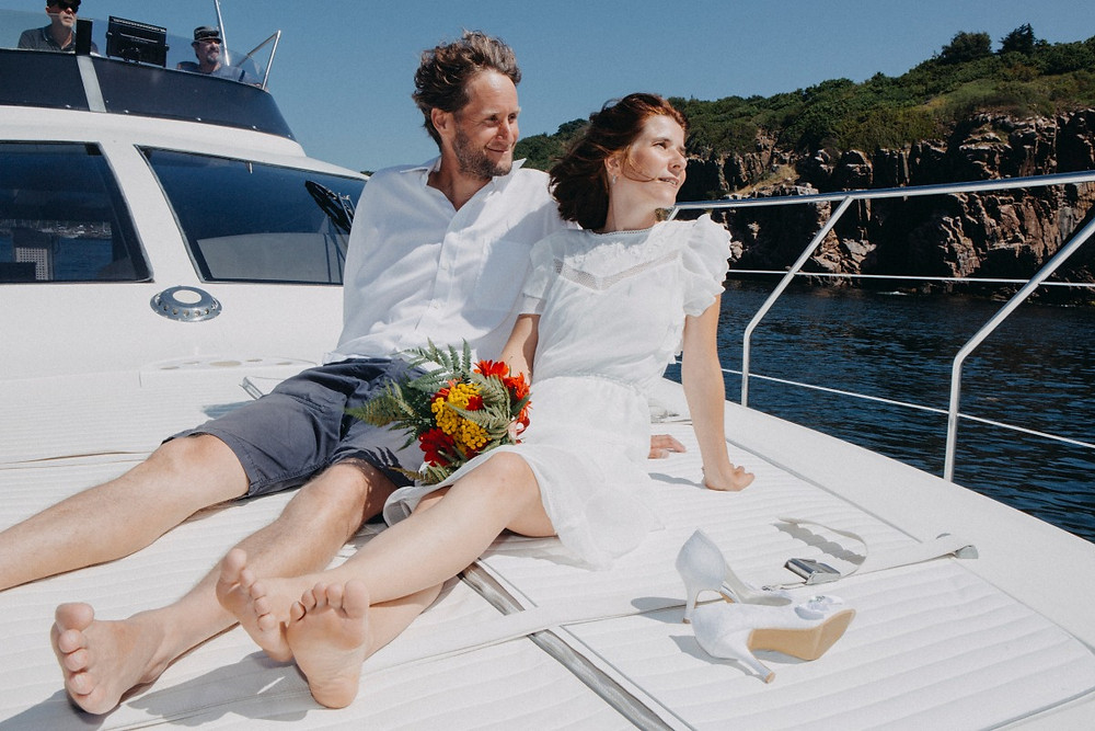 A couple sitting on the yacht floor after their intimate wedding abroad on Bornholm