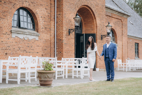 Newlyweds holding hands and walking outside of a brick castle during their micro wedding in Denmark