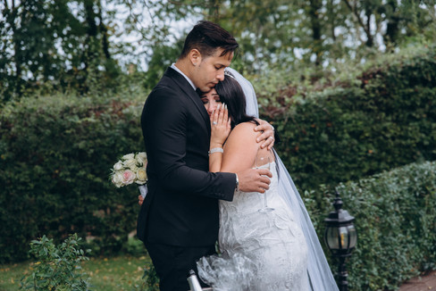 A groom holding his emotional bride as they show overwhelming joy during their overseas wedding in Lolland Island in Denmark.