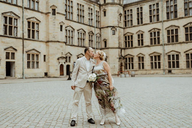 A couple kissing at Hamlet's Elsinore Castle during their small castle wedding adventure.